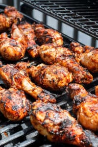 A pan of food on a grill, with Chicken and Barbecue
