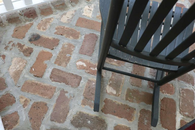 A close up of a brick porch and rocking chair