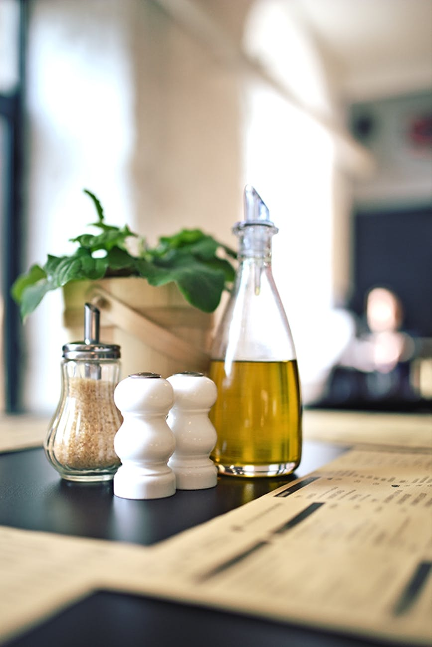 A bottle of olive oil on top of a wooden table, with Salad dressing