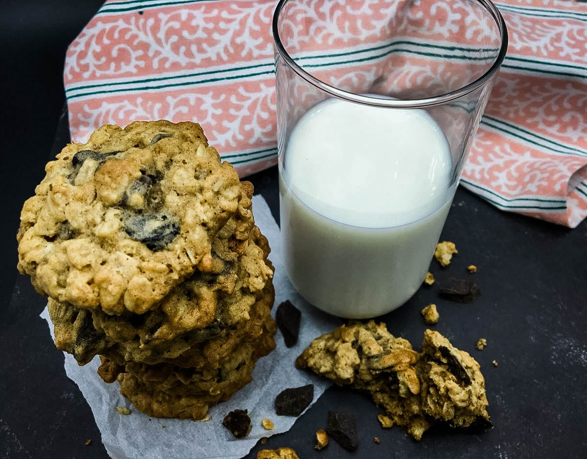 stack of cherry chocolate chunk oatmeal cookies with a glass of milk