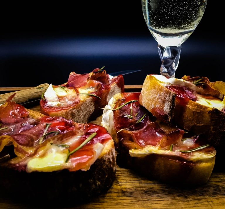 Crostini with Brie and Coppa and Raspberry on cutting board with glass of wine