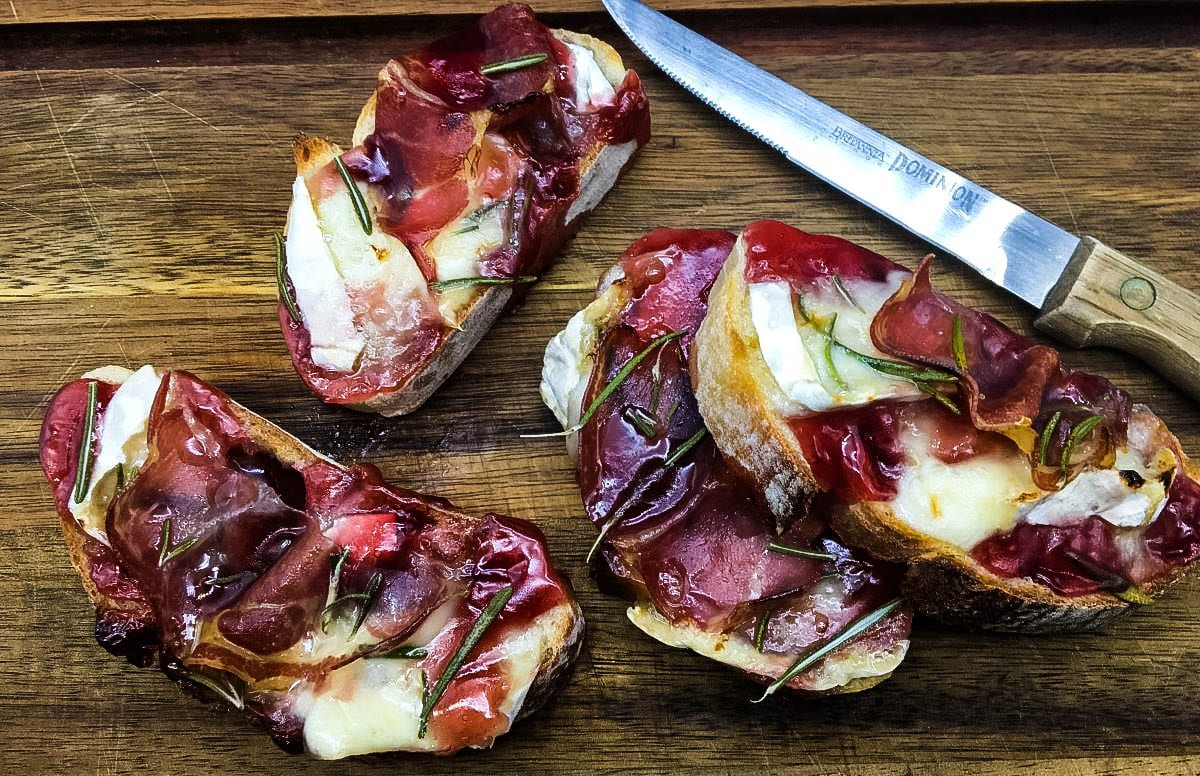 Crostini with Brie and Coppa and Raspberry on cutting board with a knife