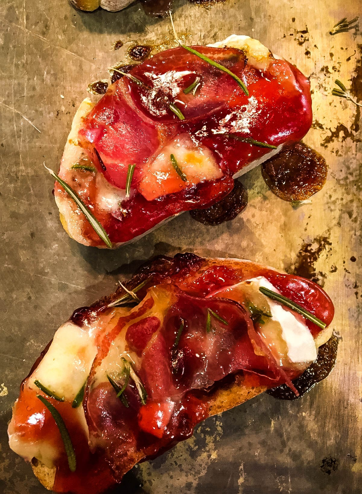 Crostini with Brie and Coppa and Raspberry on baking sheet after being broiled