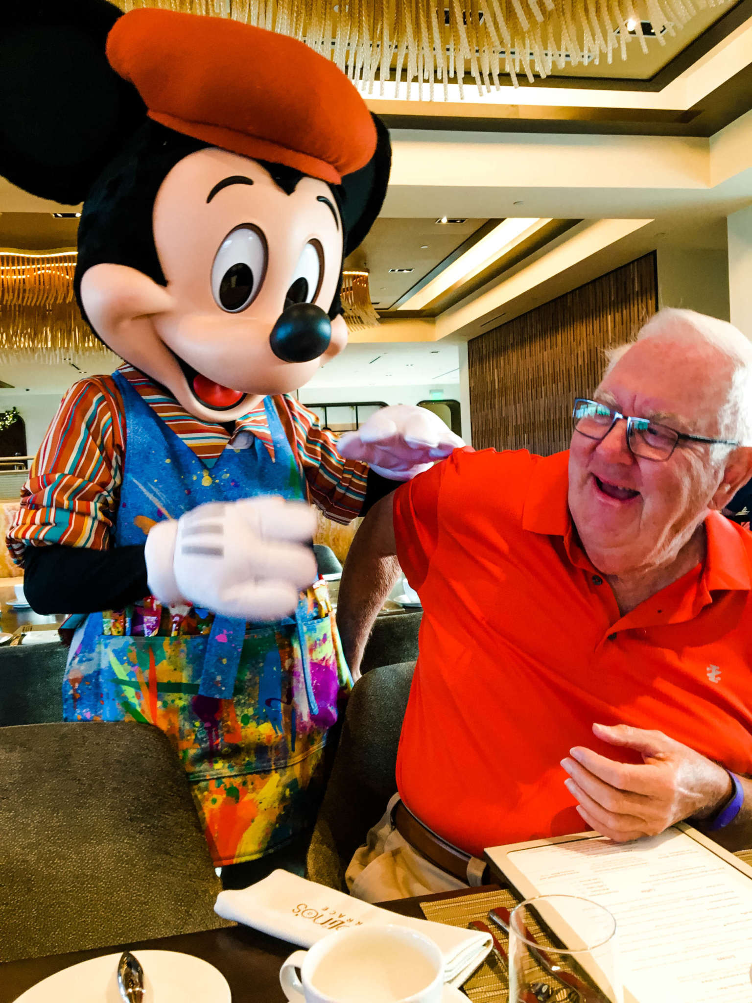A person sitting at a table with Mickey Mouse