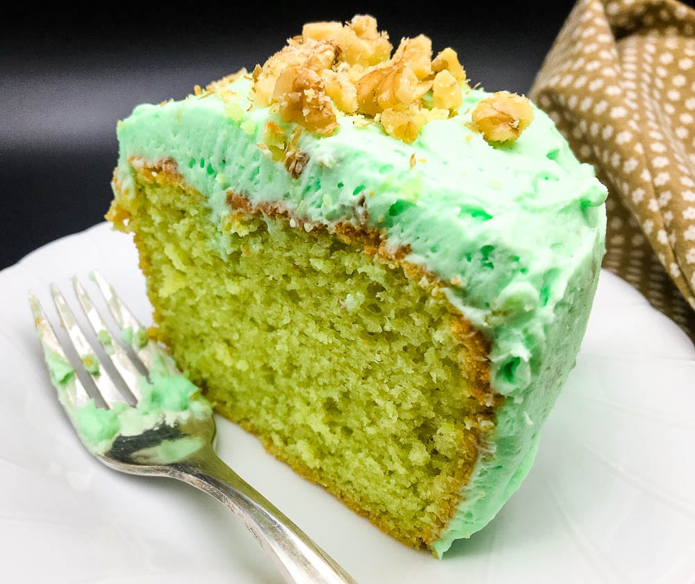 A piece of cake on a plate, with Pistachio and Cream