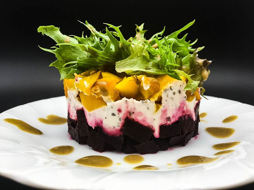 A salad of beets and cheese on a plate, with Cream and Vinaigrette