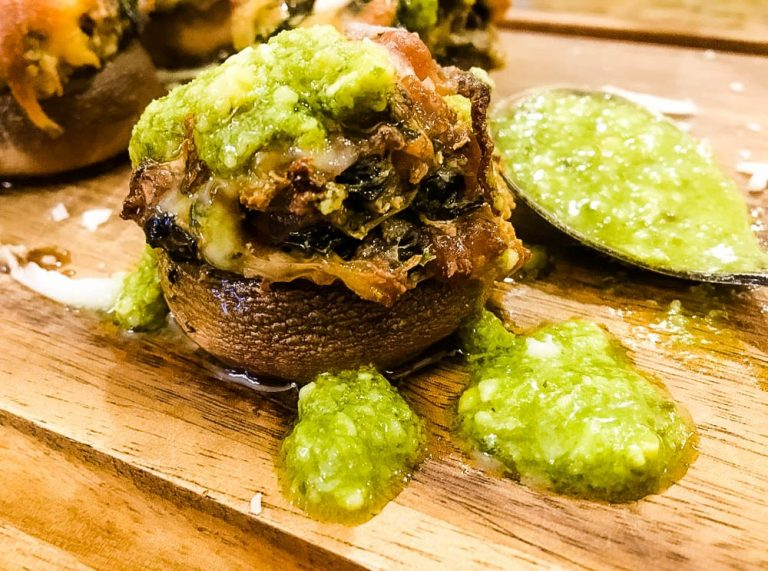 A piece of meat on a cutting board with pesto