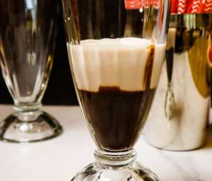 A group of clear glasses next to a glass of chocolate sauce, with Chocolate and Cream