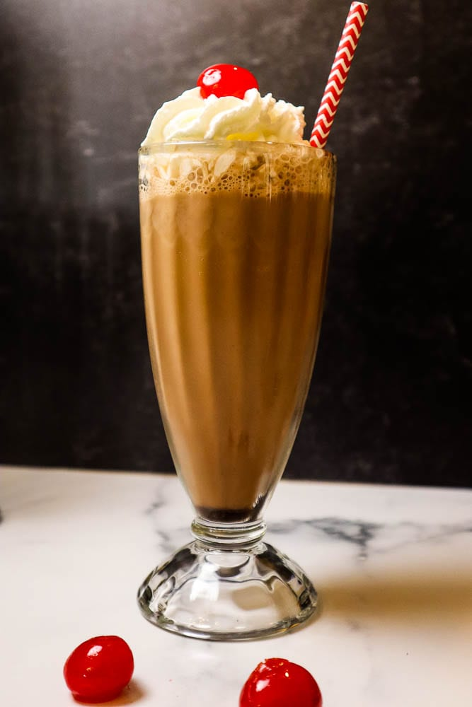 A glass on a table, with Egg cream