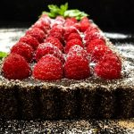 A close up of a piece of cake covered in raspberries