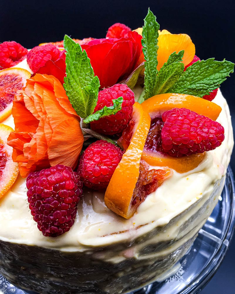 A cake with fruit on a plate, with Cream and Marmalade