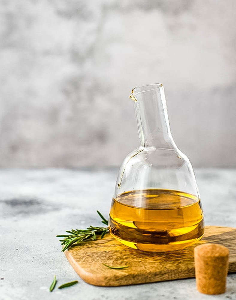 A glass bottle sitting on a table, with olive oil