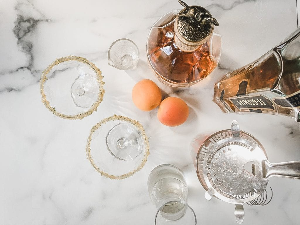 A close up of liquor bottles and fruit, with Apricot and Fizz