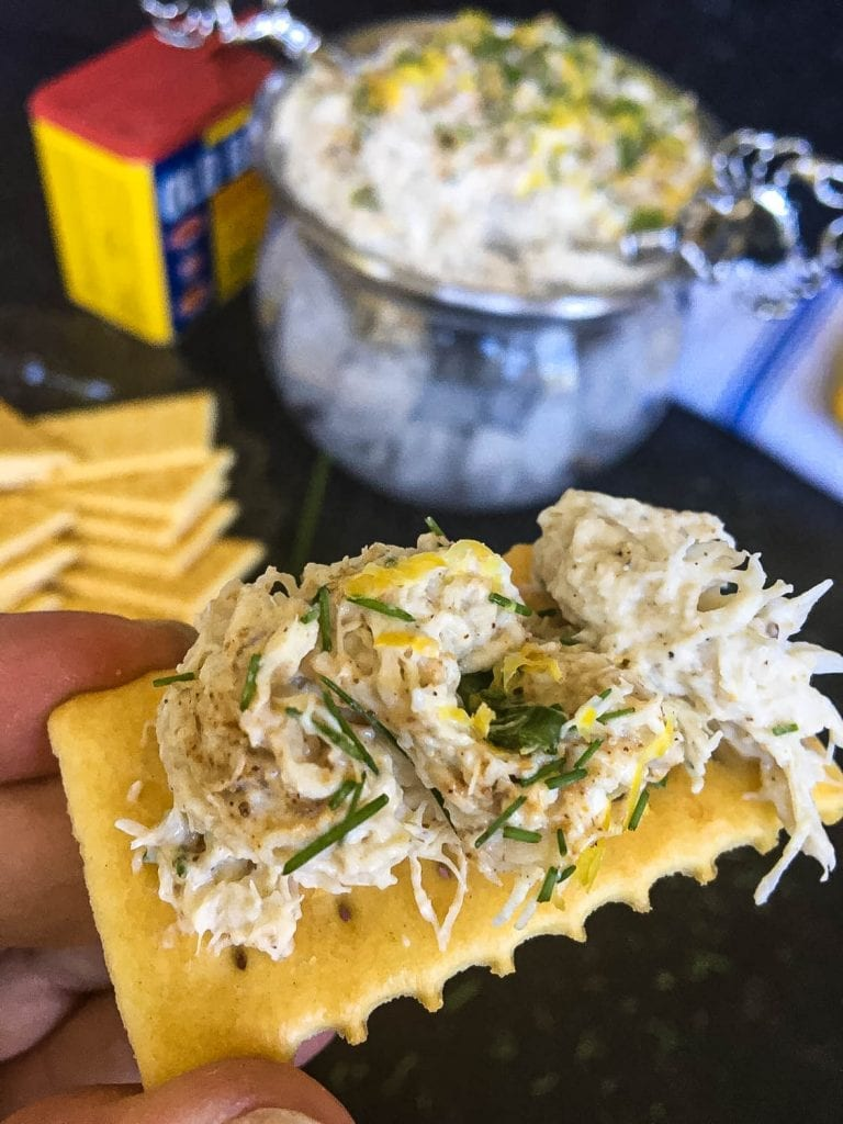 A close up of dip on a cracker, with Crab dip