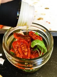 A jar of food on a table, with Tomato
