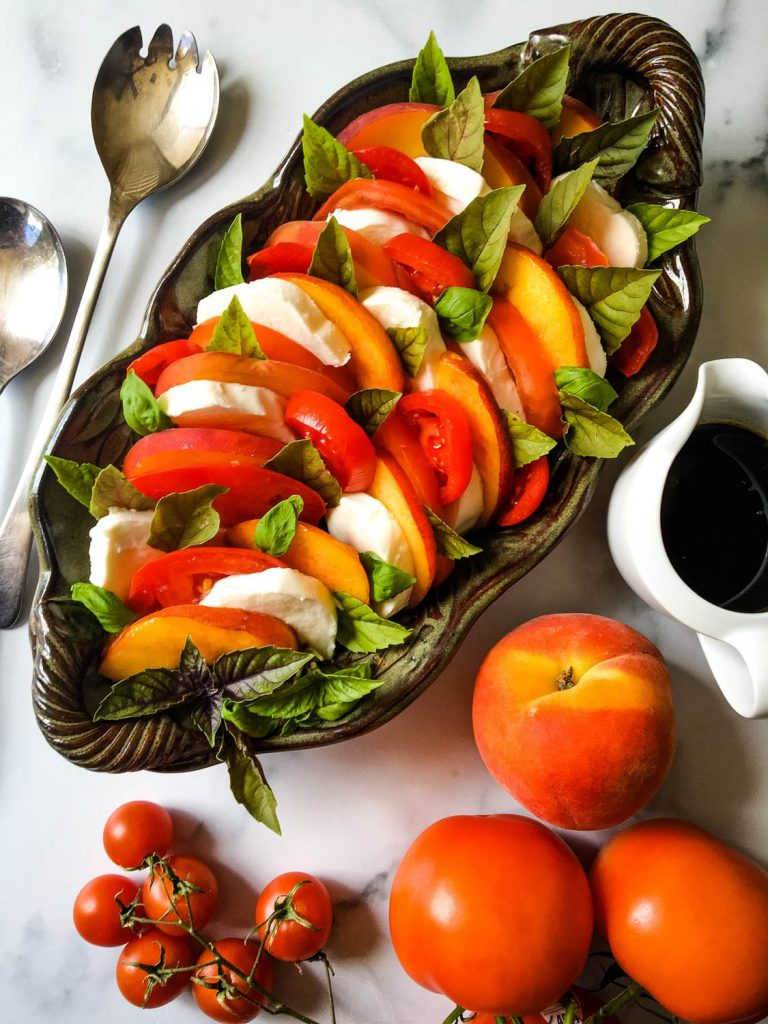 Many different types of food on a table, with Peach and Salad