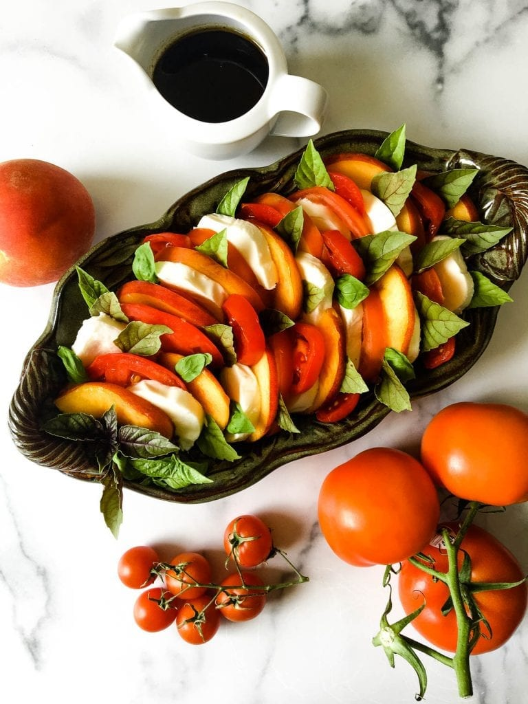 A bunch of food on a table, with Salad and Peach