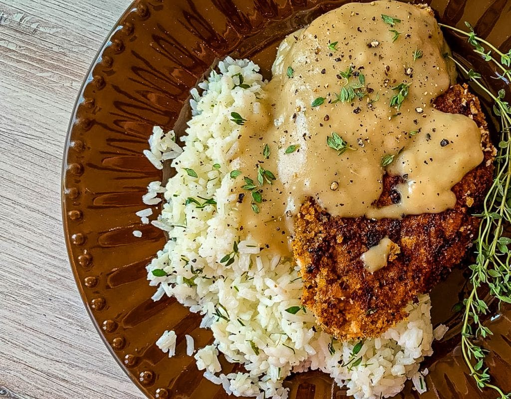 A close up of a plate of food with Rice chicken and gravy