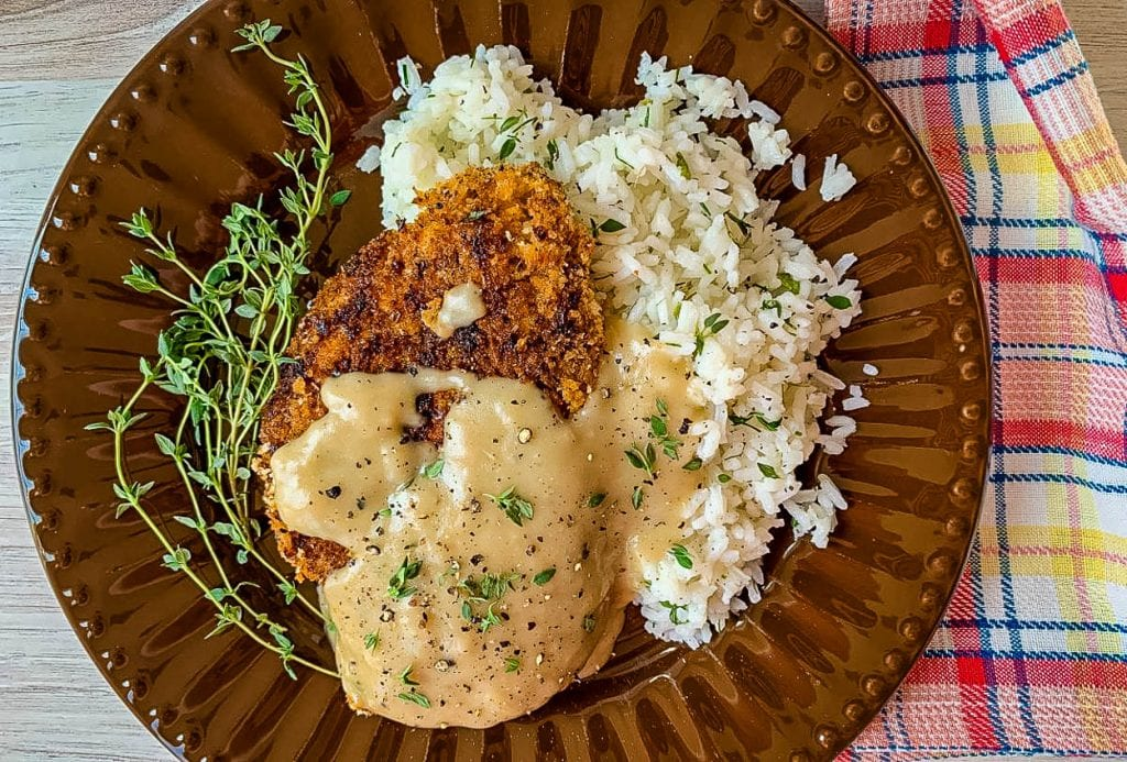 a brown plate, with chicken and rice