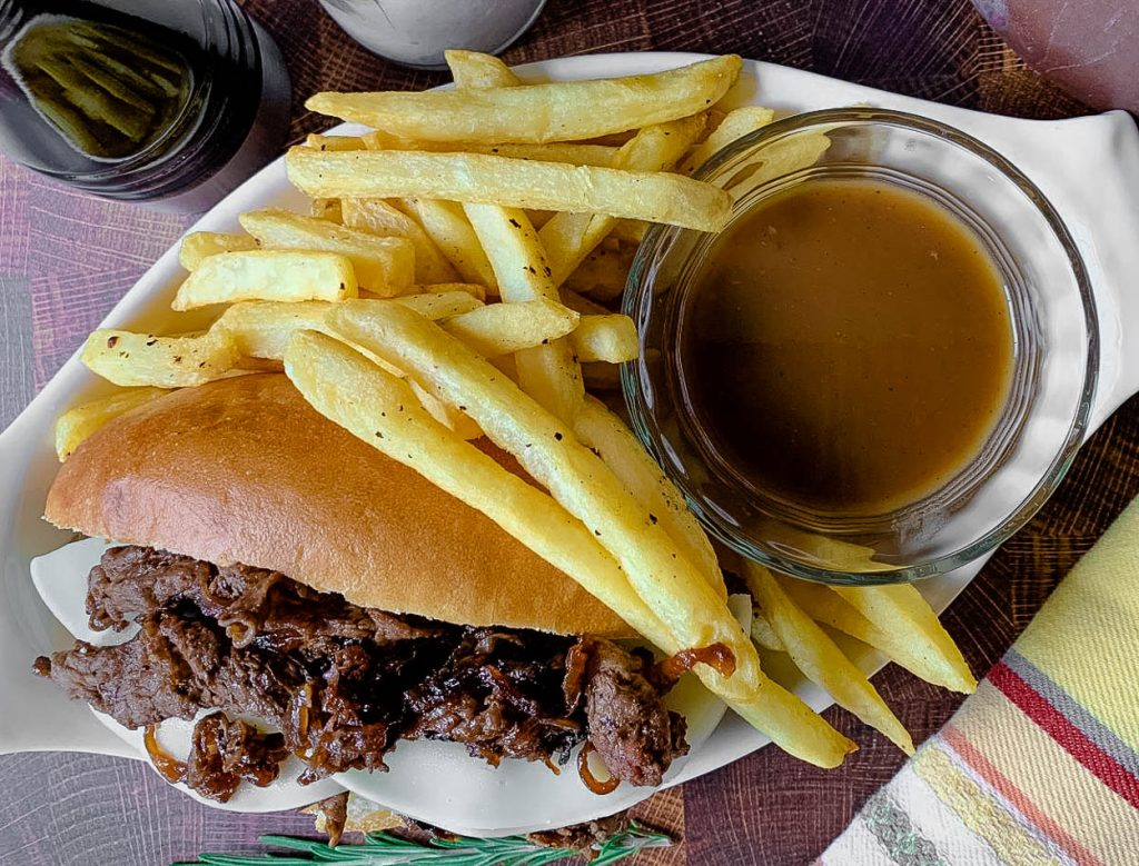 A sandwich and fries on a plate, with French dip and Roast beef