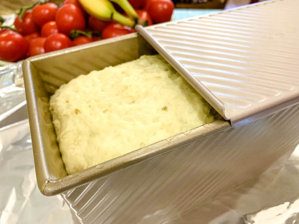 An unbaked loaf of bread in a bread pan