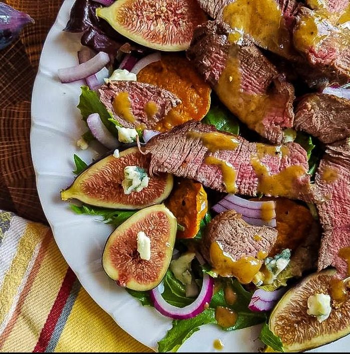 A plate of food on a table, with Salad and Beef