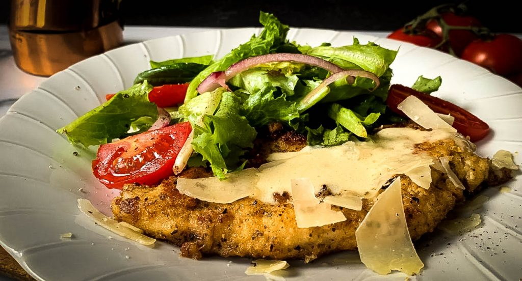 chicken cutlet with side of salad and parmesan cheese
