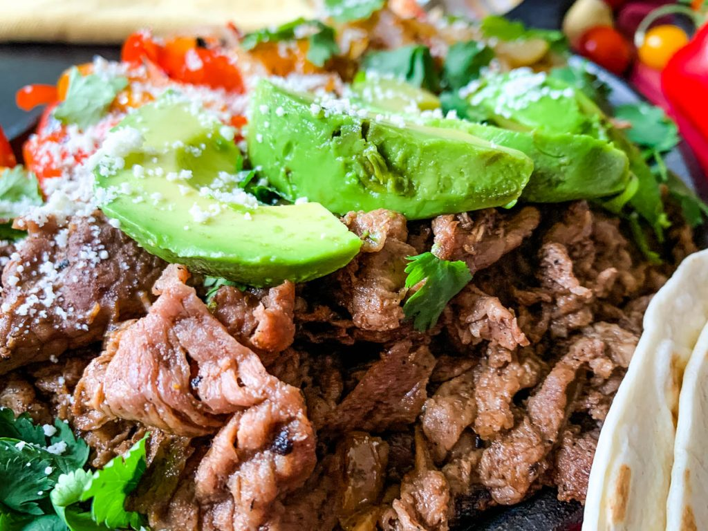 up close of beef and avocado in tender shaved beef fajitas