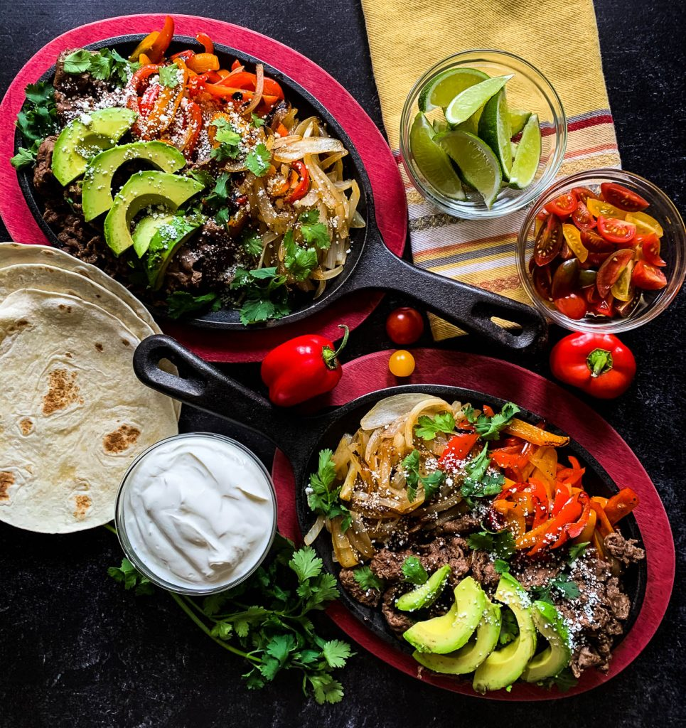 two sizzling iron pans of tender shaved beef fajitas with tortillas and lime wedges