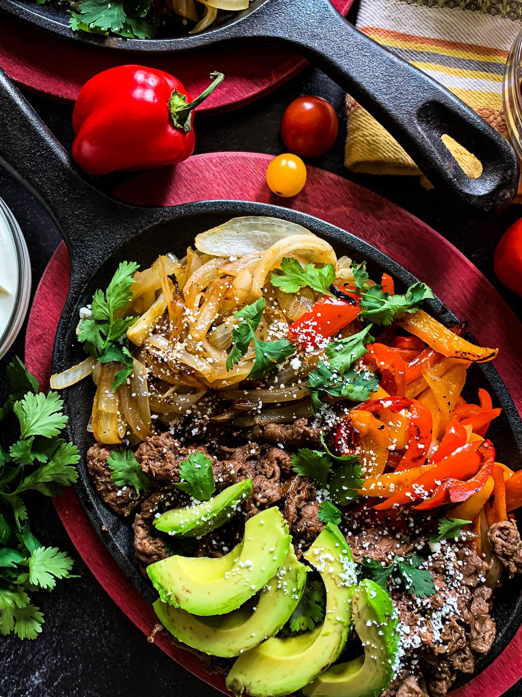 sizzling iron pan of shaved beef fajitas