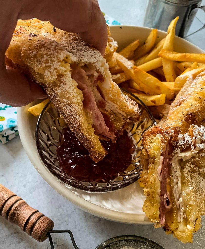 hand dipping Monte Cristo sandwich into raspberry jam