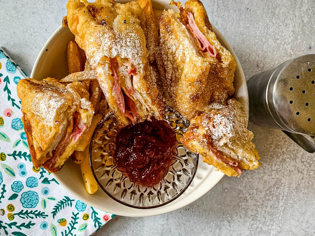 close up of the original monte cristo fried sandwich in a bowl with French fries