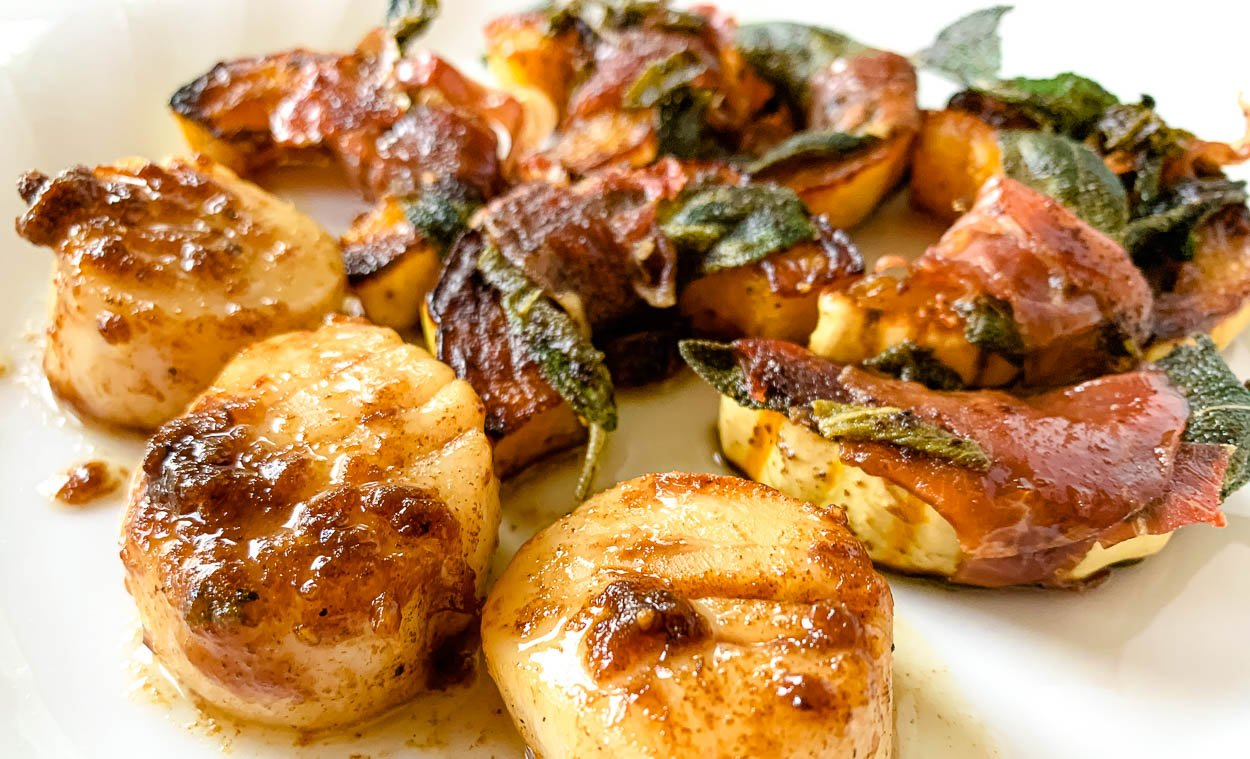 scallops seared in a hot pan with squash prepared saltimbocca style