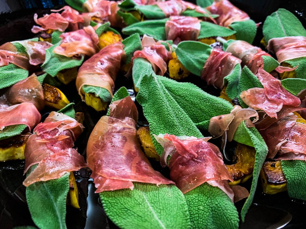 delicate squash with fresh sage leaves wrapped in prosciutto before being roasted