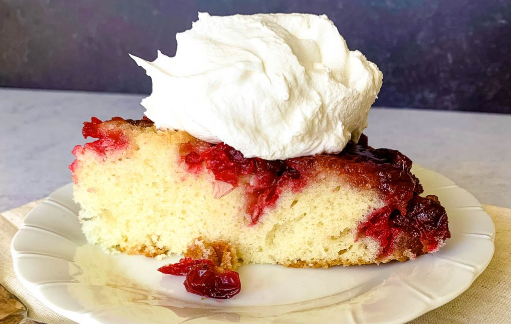 a slice of cast iron cranberry cake with whipped cream on the top