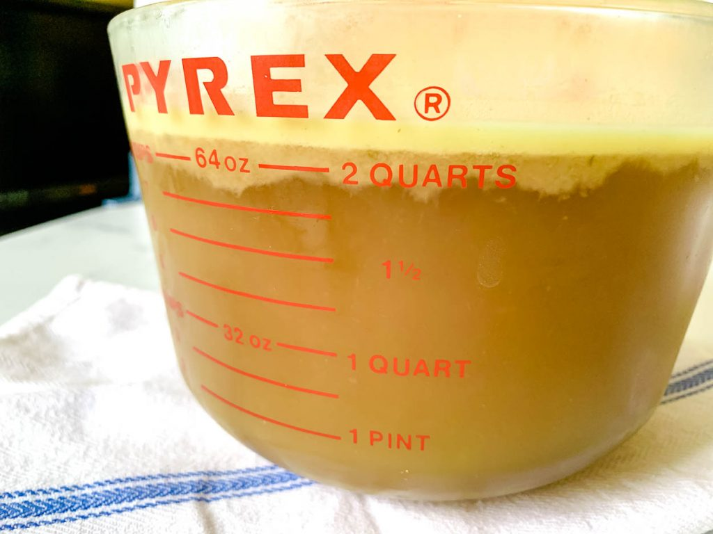 a glass measuring cup filled with ham stock