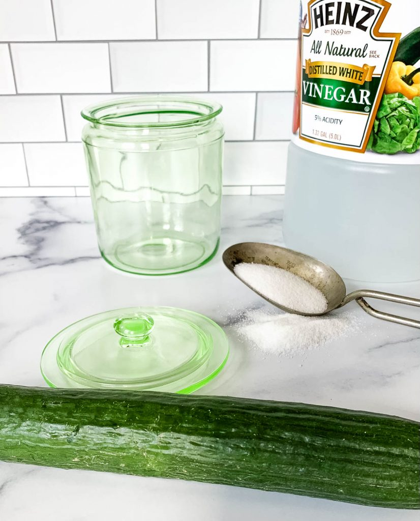 a jar, a lid, a bottle of vinegar, a scoop of sugar, and a cucumber on a white counter
