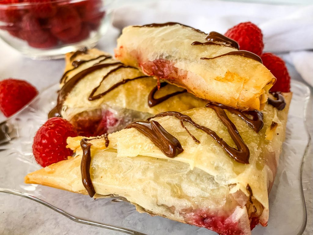 galss plate with three 3 Ingredient Chocolate Raspberry Turnovers on it and scattered whole raspberries