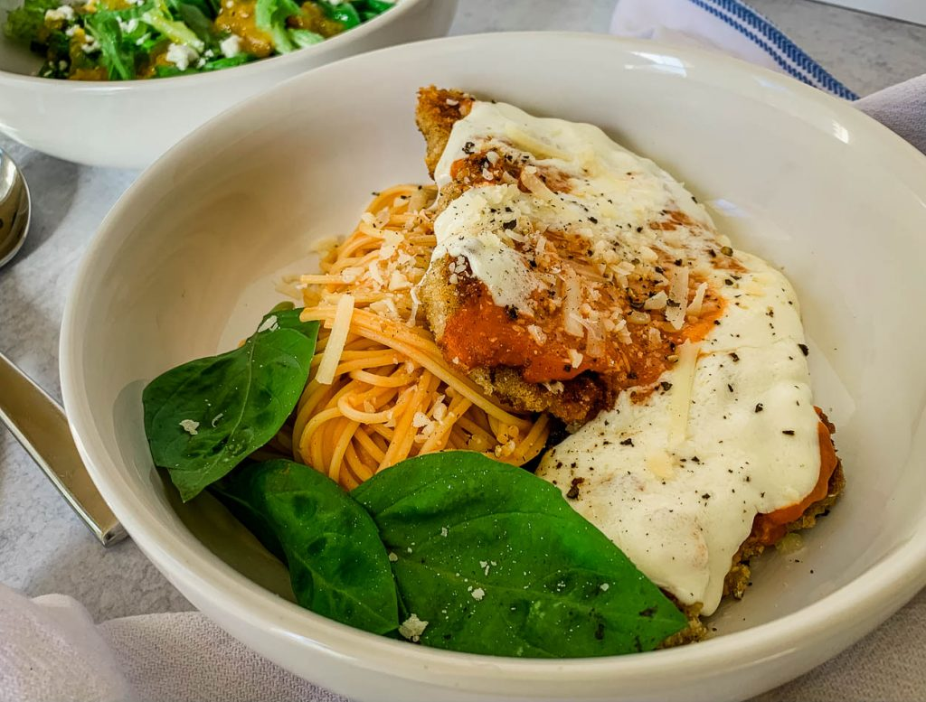 Favorite Quick 'n' Easy Crispy Pork Cutlets Parmigiana in a white bowl on a white counter