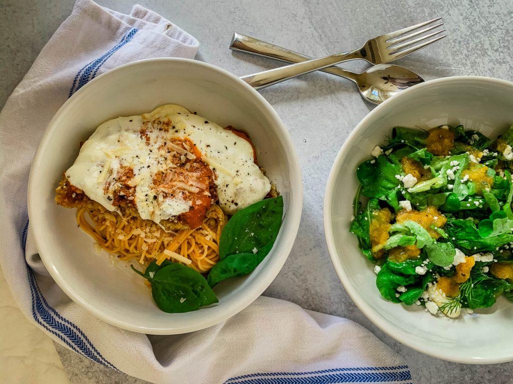 Favorite Quick 'n' Easy Crispy Pork Cutlets Parmigiana shown alongside a bowl of salad