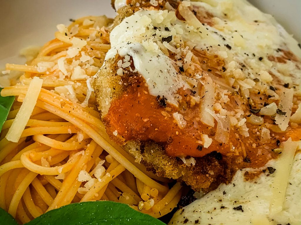 close up of Favorite Quick 'n' Easy Crispy Pork Cutlets Parmigiana and cooked pasta