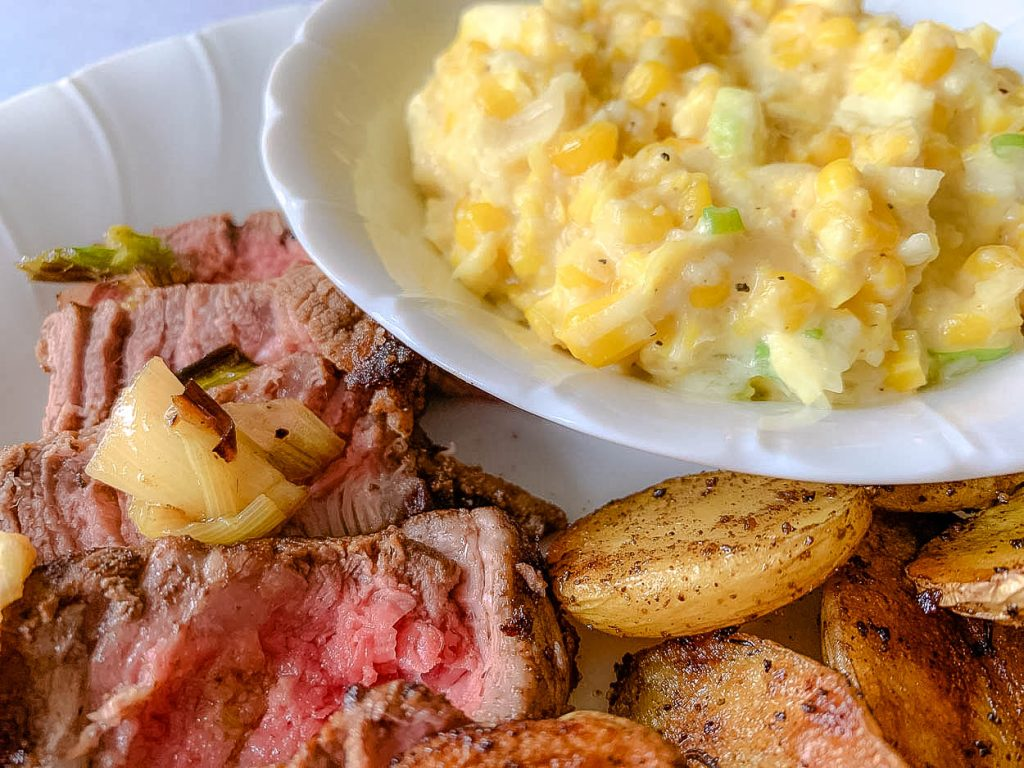a dish of creamed corn on a plate with grilled potatoes and meat