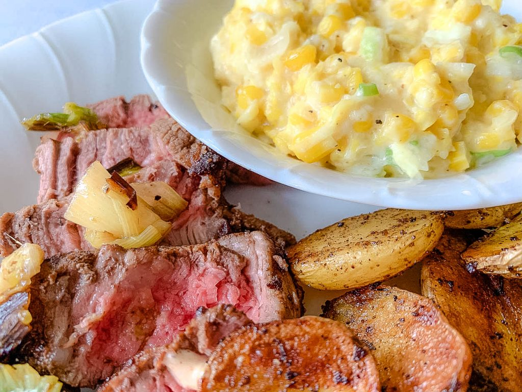 white plate with corn and steak and patatas bravas