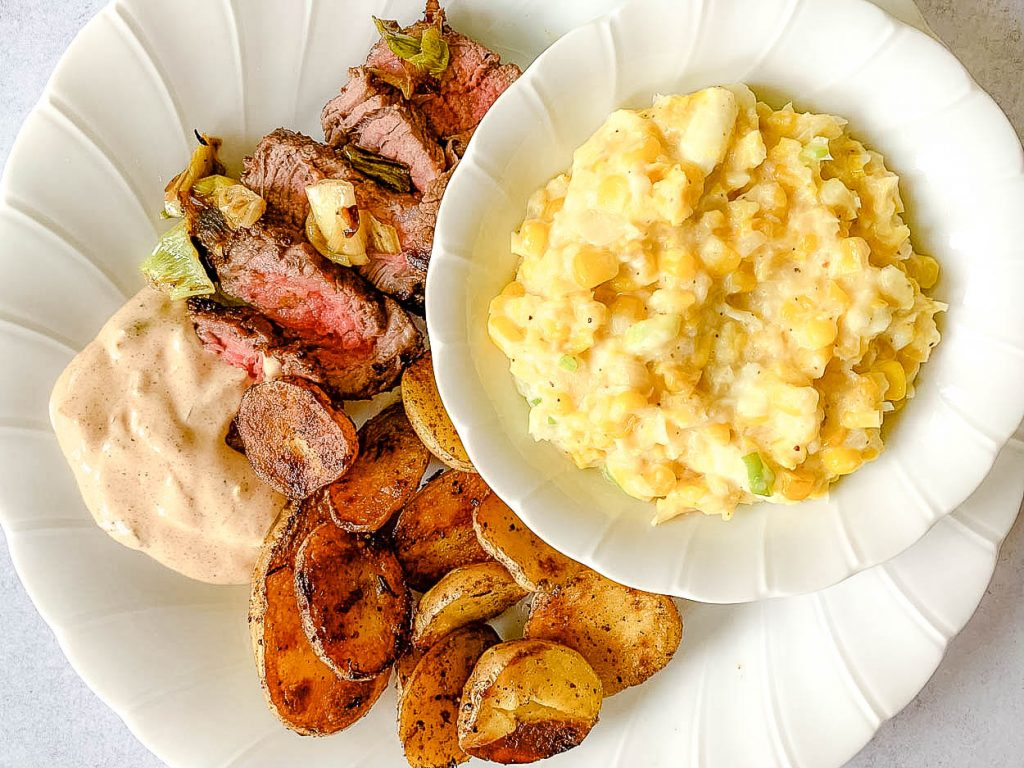 plate of steak and potatoes with bowl of creamed corn