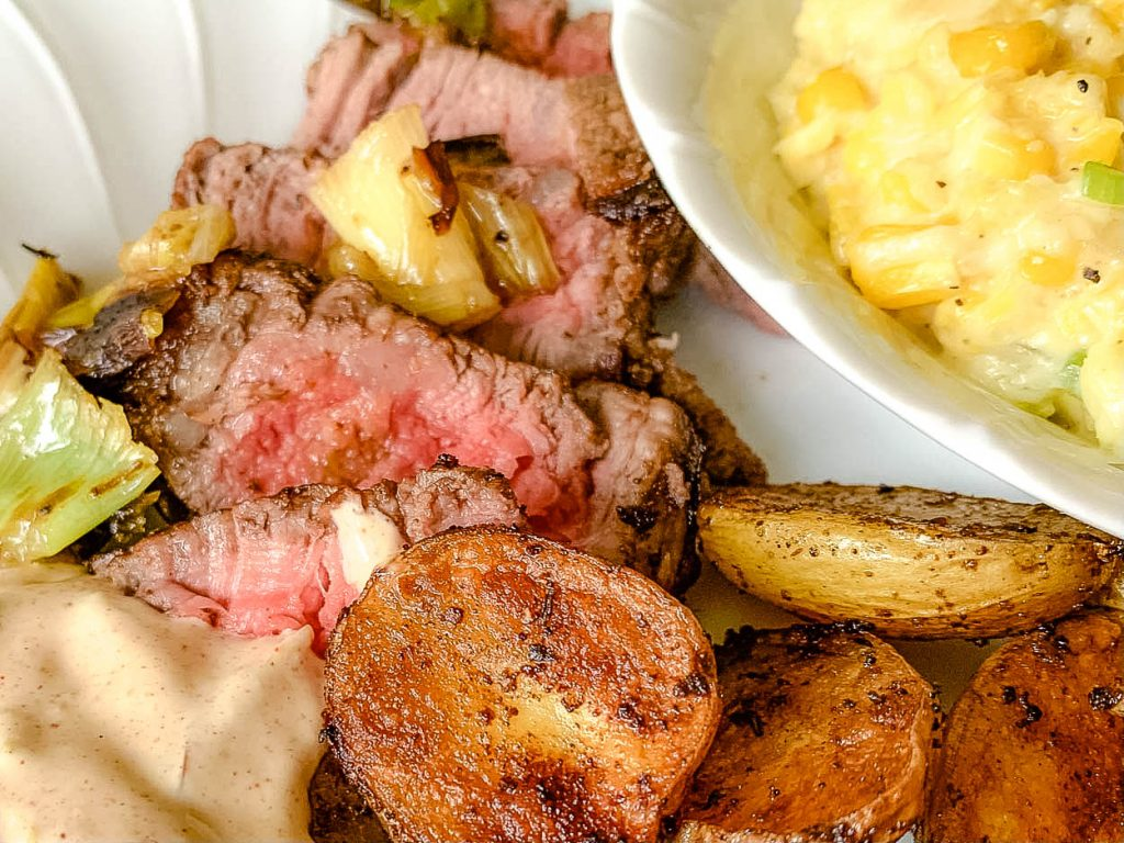 white plate with steak and potatoes and corn