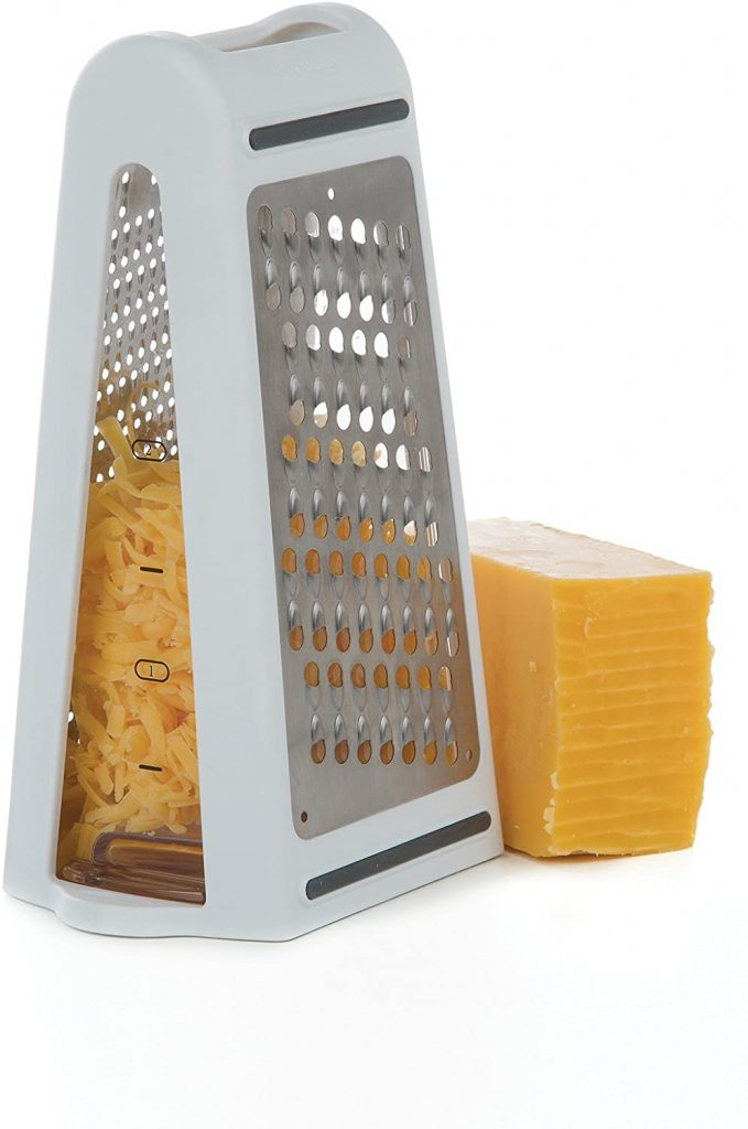 grater with built in measurer with a piece of cheese on top