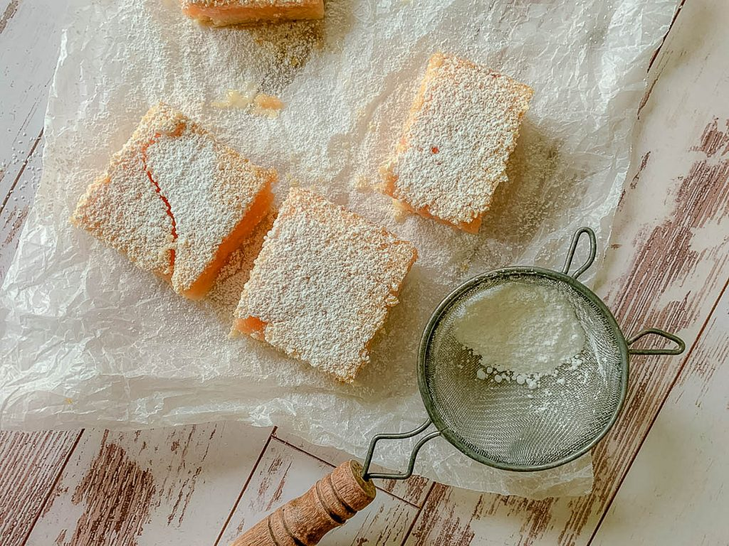 overhead photo Blissful And Indulgent Creamy Pink Grapefruit Bars on wood surface