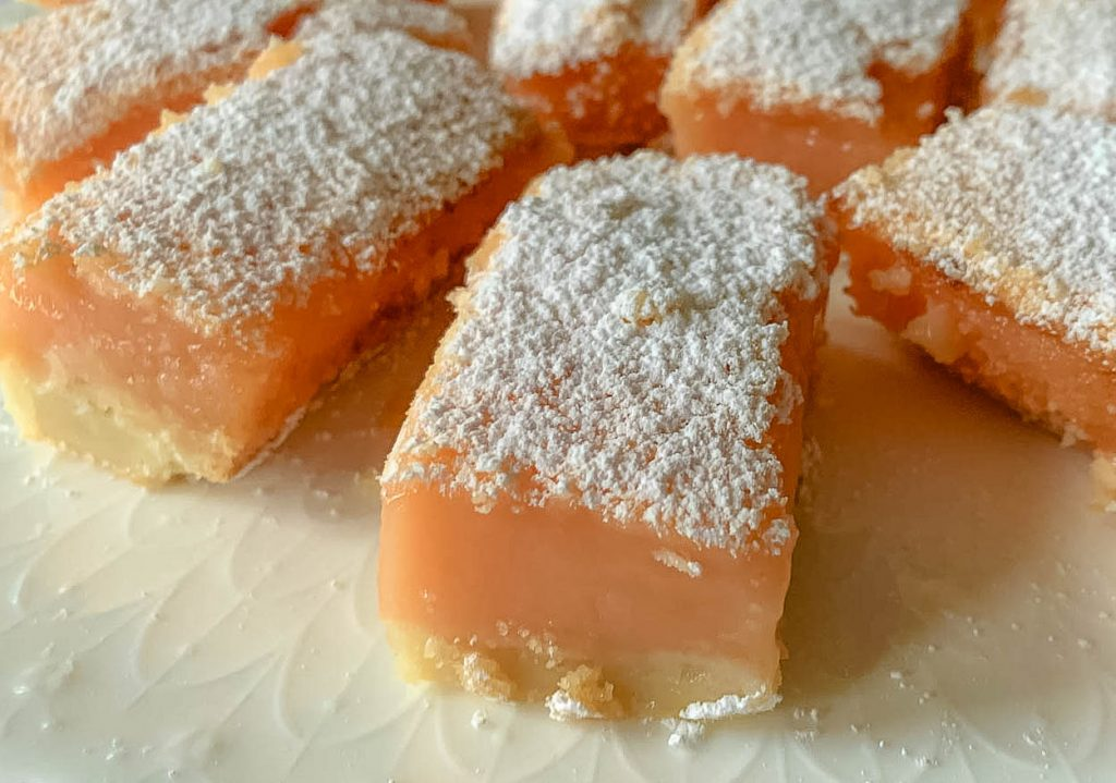 close up of Blissful And Indulgent Creamy Pink Grapefruit Bars on white plate