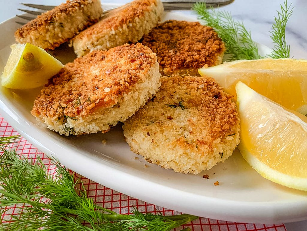 A bunch of Cackalacky Chicken Cakes on a white platter, with Lemon and Dill