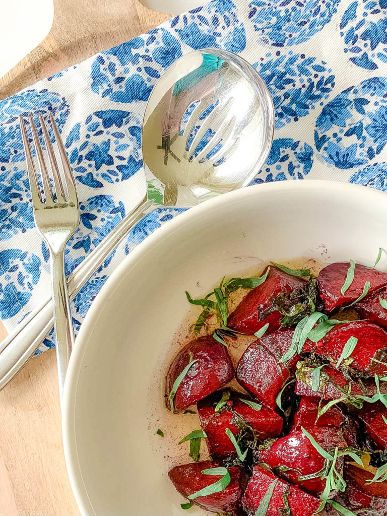 a white bowl with beets , with blue napkin and spoons